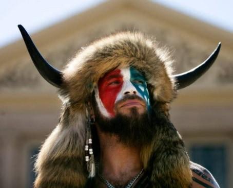 Attacco Washington Jake Angeli, volto dipinto, senza mascherina, il megafono in mano e una finta pelle di bisonte cornuto sulla testa. Jake ha affermato che il suo compito è quello di spiegare alle persone le sue convinzioni su QAnon e altre verità che dice rimangono nascoste
