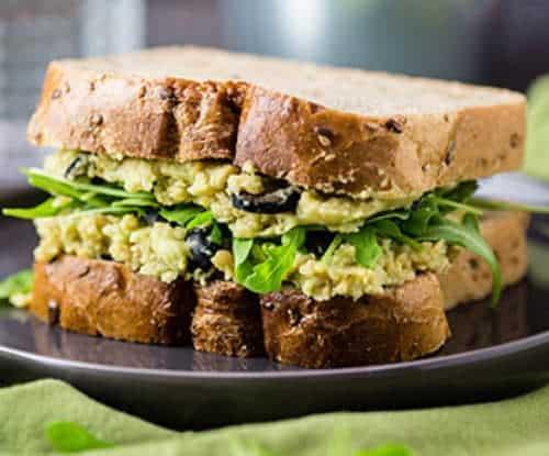 Sandwich ripieno crema ceci e avocado, con olive e rucola